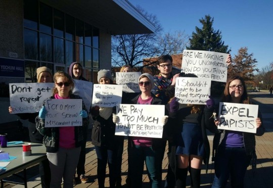 Student demonstrators raise signs to spread awareness of the issue of sexual assault on Capital's campus.