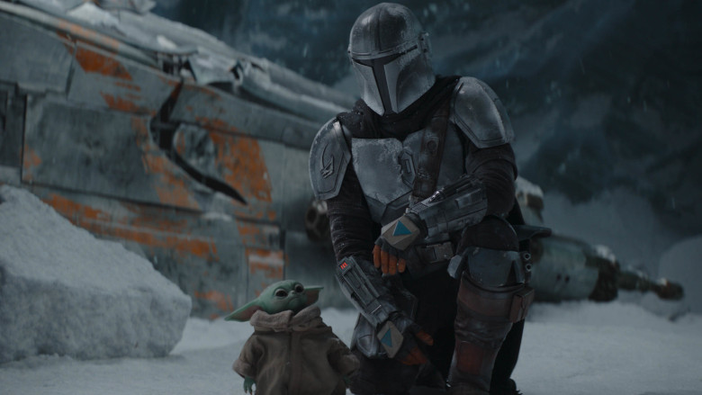 Baby Yoda (left) and the titular character of The Mandalorian (right) in a snowy environment.