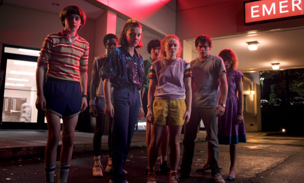 Main characters of Stranger Things in front of a hospital, looking concerned.