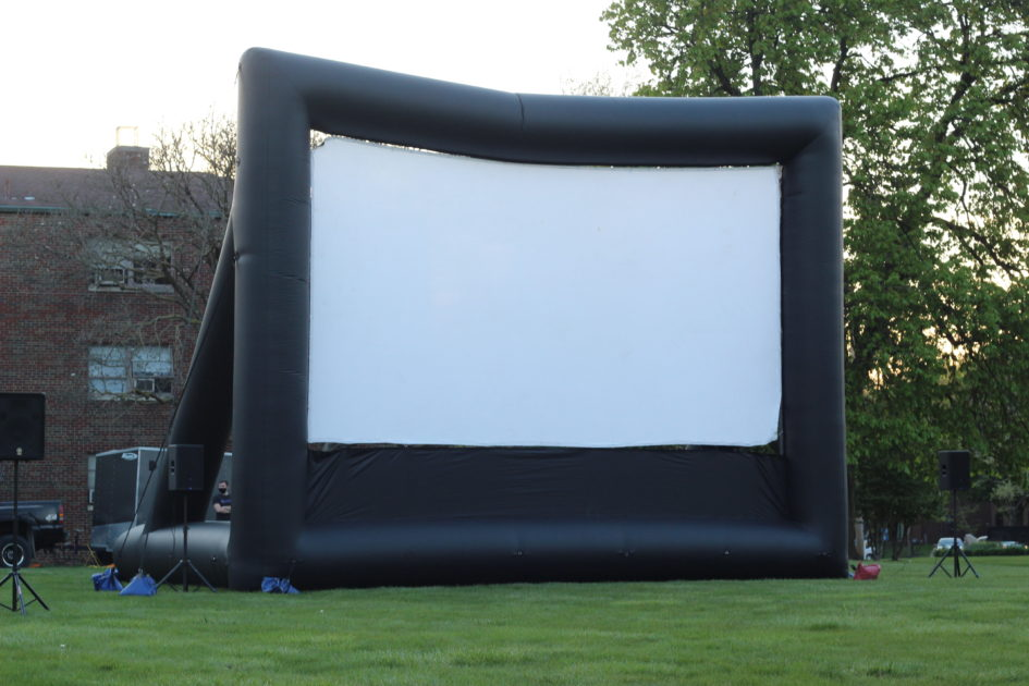 Displayed is a large projector screen that the film was shown on.